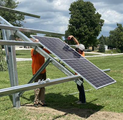 Workers from Straight-Up Solar put the first of 28 solar panels up Monday