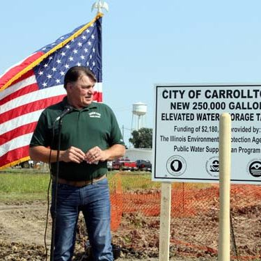 Carmen Ensinger/Greene Prairie Press Carrollton Mayor Mike Snyder welcomes everyone to the groundbreaking ceremony of the city's new water tower which will be located on the west side of town near the FS plant. Flanked by the American flag on the left and the sign describing the project, take note that the city's present water tower can be seen in the background. The new tower is expected to be up and go online next summer or early fall.