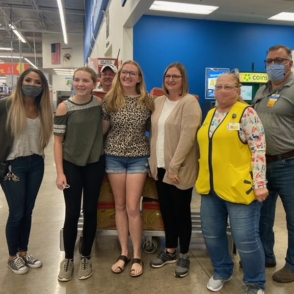 Submitted photo LeaAnn Klaas with her daughters, Taylor and Hannah, along with her brother Lonnie Clowers and the Walmart staff who assisted her with the Power Pack Program that she founded to provide weekend food for children in need.